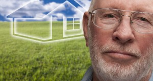 Melancholy Senior Man with Green Grass Field and Ghosted House Behind Him.