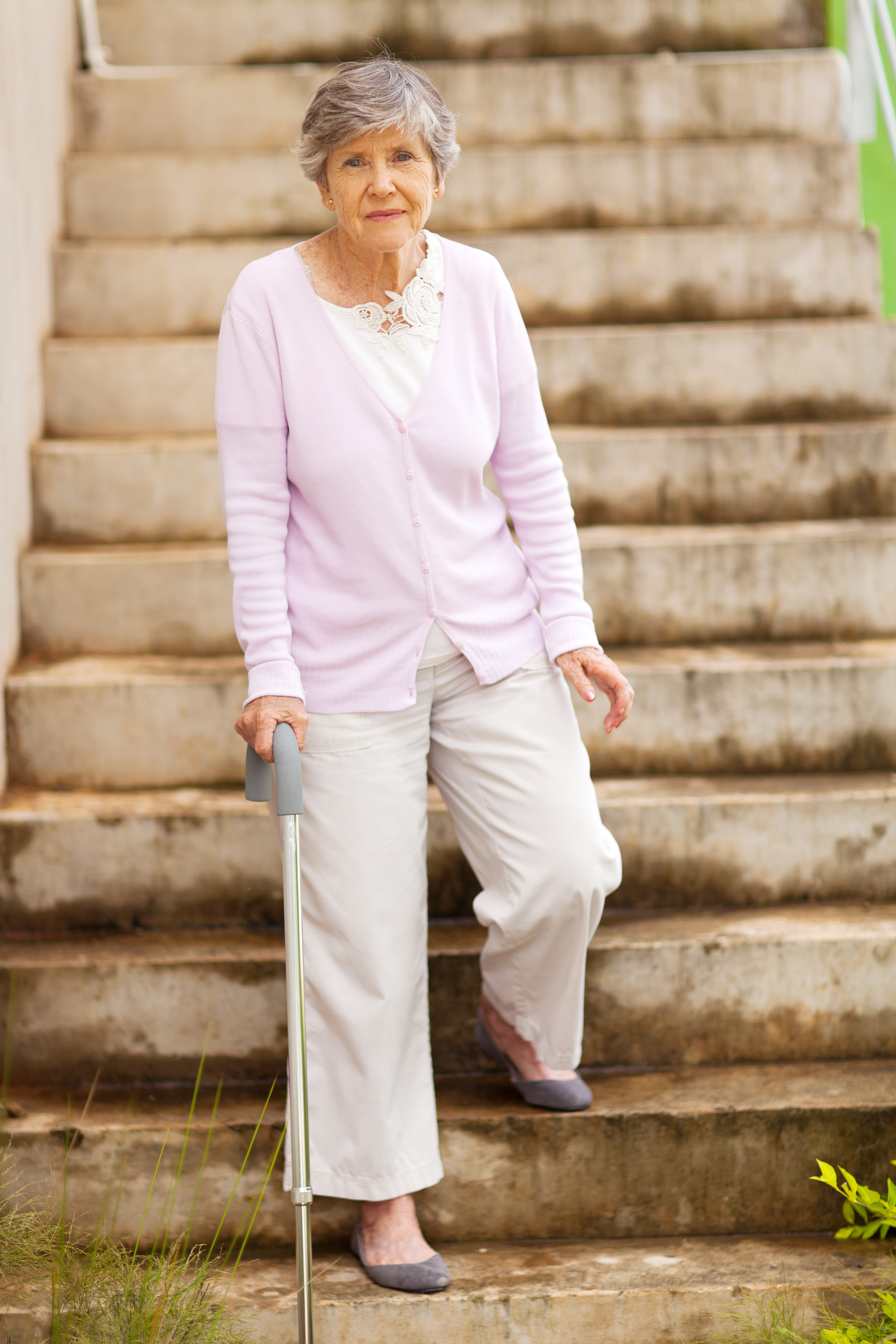 lonely senior woman standing by stairway
